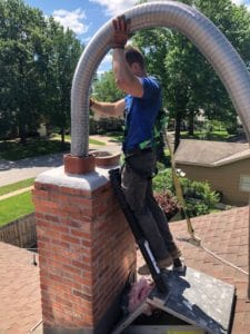 Certified Chimney Sweep Inserts a 316Ti Alloy Liner into a Gas Chimney Flue