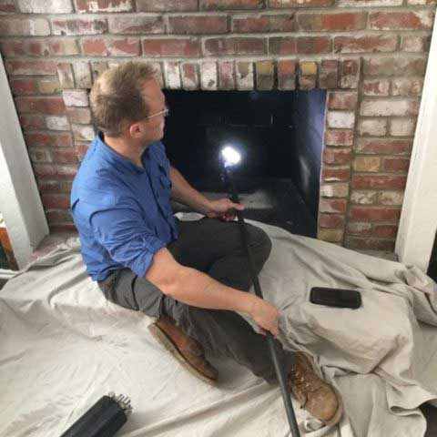 Fireplace-Inspector-performing-fireplace-cleaning-and-inspection