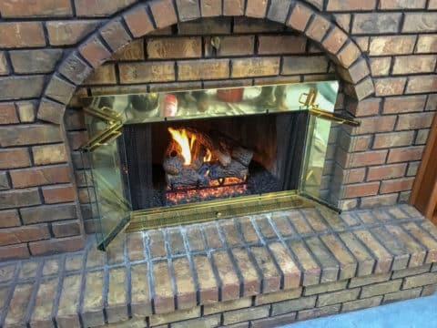 Gas logs installed in masonry fireplace with glass doors