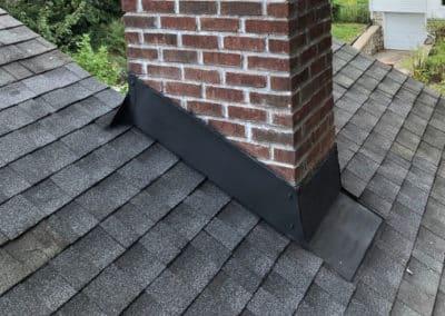 black chimney flashing on brick chimney