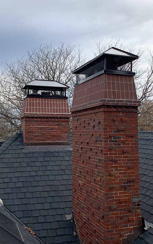 Two Brick Chimneys Black Steel Caps