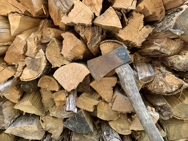 pile of wood logs with axe