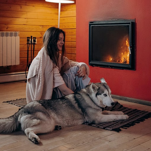 Fireplace with Lady and Dog sitting on a rug that is NOT fire safe.