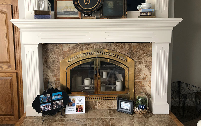 Gold Glass Doors on a White Mantel Fireplace with Candles