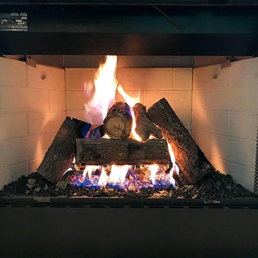 Gas logs in prefabricated firebox